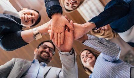 Pessoas sorrindo com as mãos unidas no meio | Importância de manter a motivação dos funcionários
