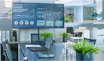 ambiente de escritório com mesa, vaso de plantas, computadores e televisão | Como tornar a sua empresa mais atrativa e lucrativa?